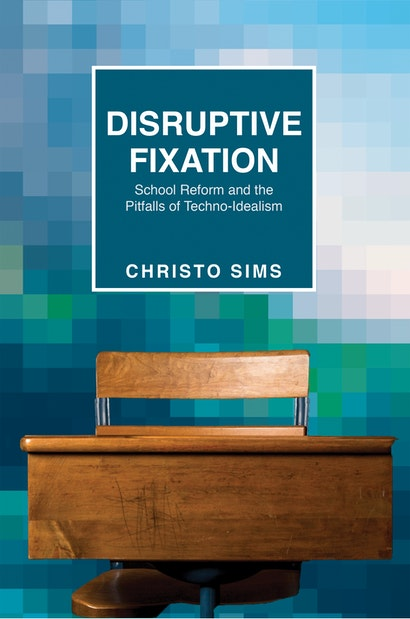 """An empty desk on a blue bacground, the cover for """"Disruptive Fixation"""""""