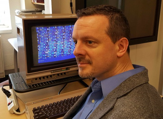 Nick Montfort in front of a Commodore 64 running one of his programs.