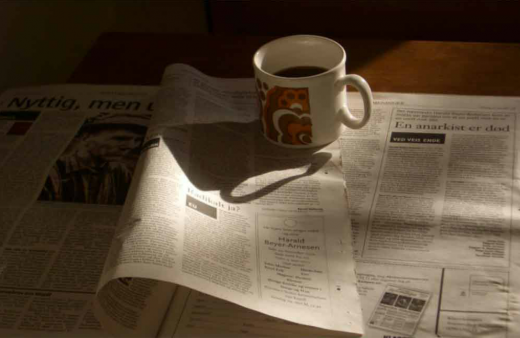 The first image seen in En anarchist er død is a photo of a newspaper, open to an obituary, with a coffee cup. The camera moves in closer.